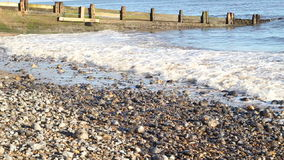 Waves breaking on a shingle beach with sound. stock footage
