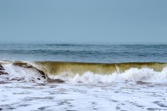 Waves breaking on the shore. With overcast sky stock images