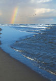 Waves Breaking on Shore with a Partial Rainbow Royalty Free Stock Photos