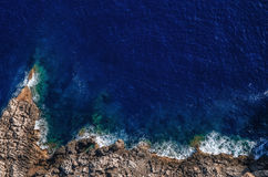 Waves breaking on the shore rocks with sea foam. Mallorca Stock Images