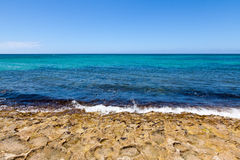 Waves breaking on shore of tropical island. Gentle waves on the shore of a tropical island in the Pacific Ocean. Deep and vibrant blue ocean colors Stock Photo