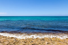 Waves breaking on shore of tropical island. Gentle waves on the shore of a tropical island in the Pacific Ocean. Deep and vibrant blue ocean colors Stock Image