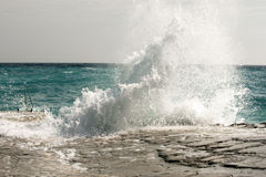 The waves breaking on a stony beach, forming a spray Stock Photography