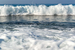Waves breaking on a stony beach, forming sprays Royalty Free Stock Images