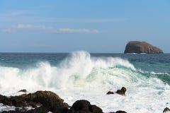 Waves breaking on a stony beach Stock Photos