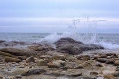 Waves breaking on a stony beach royalty free stock photography