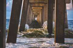 Waves breaking under pier Royalty Free Stock Photography