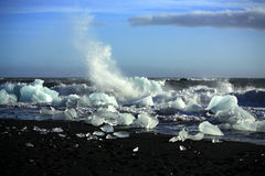 Waves breaking up the icebergs. On the beach Iceland Royalty Free Stock Photos