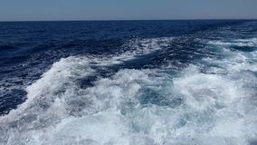 Waves and bubbling water behind a fast floating yacht stock video footage