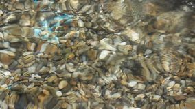 Waves of clear water over gravel stock footage