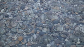 Waves and clear water. Through the water are visible stones. Rivers, lakes and the sea. stock footage