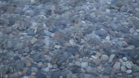 Waves and clear water. Through the water are visible stones. Rivers, lakes and the sea. stock video