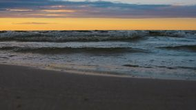 Waves closup on Baltic sea Atlantic ocean in evening sunset twilight light. Dramatic sunset twilight with rainy clouds on calm Baltic sea evening coastline stock video
