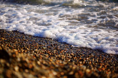 Waves and coastal pebbles at sunset Stock Photography