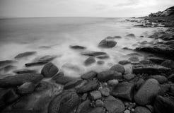 Waves on coastal rocks. Waves washing ashore over rocks along a rugged coastline Stock Image