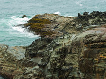 Waves at colorful, textured rock cliff Stock Image
