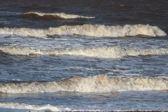 Three waves coming ashore on beach at Fleetwood. Waves coming ashore on the beach at Fleetwood on the edge of Morecambe Bay, Lancashire, England on a windy royalty free stock image