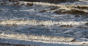 Small waves coming ashore on beach at Fleetwood. Waves coming ashore on the beach at Fleetwood on the edge of Morecambe Bay, Lancashire, England on a windy stock photography