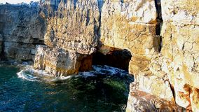 Waves coming through a natural hole in a cliff, Boca do inferno stock video footage