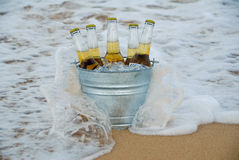 Waves Crash Against a Bucket of Ice Cold Beer stock images