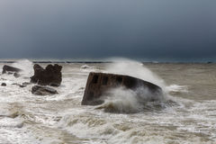 Waves crash against the forts in a stormy sea Stock Photo