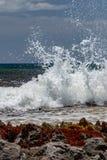 Waves crash against rocks in caribbean sea stock photography