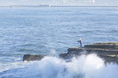 Waves crashing around surf fisherman on rocky shore in Ocean Bea. Waves crash against the rocky cliffs of Ocean Beach, California as a surf fisherman fishes from Royalty Free Stock Images