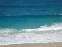 Waves crash on along beach Stock Photos
