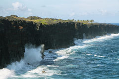 Waves crash along the black lava rock cliffs. In the Hawaiian Volcanoes National Park.   This view is at the end of the Chain of Craters Road Stock Image