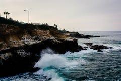 Waves crash on cliffs along the Pacific Ocean in La Jolla, Calif stock photos