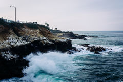Waves crash on cliffs along the Pacific Ocean stock images