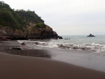 Waves crash on dark sand beach in Manzanillo, Mexico. Waves crash on empty dark sand beach in Manzanillo, Mexico with a rock island and rocky cliff surrounding Stock Images