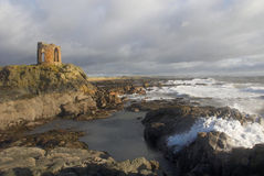 Waves crash on fife shore below Lady's tower. Waves crash onto shore at Lady's Tower, Elie, Fife, Scotland as a storm clears stock image