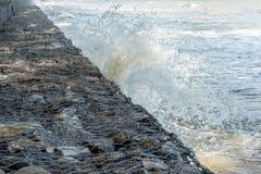 Waves crash into long stone seawall Royalty Free Stock Image