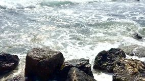 Waves crash onto rocks and breaks up to mist. Slow motion clip of waves crash onto rocks and breaks up to mist in the wind on a stormy winter day in Mallorca stock video footage