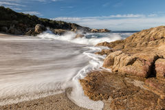 Waves crash onto a small sandy cove near Calvi in Corsica Royalty Free Stock Images