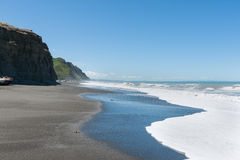 Waves crash onto South Pacific beach lined with cliffs bin New Z Stock Image