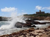 Waves crash into rock; lighthouse in background. Waves crashing into rocks and beach surrounding the Lighthouse of Puerto Ferro on Vieques Puerto Rico royalty free stock photography