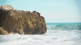 Waves crash. On the rocks. Beautiful shot and georgous highleted waves. Perfect clear blue clean water. Rocks cause large sprays of water when the waves slam stock footage