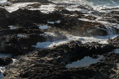 Waves crash on the rocks off the coast at Cape Perpetua Special Interest Area where Thor`s well is located royalty free stock photo