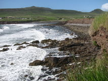Waves crash on rocky shore line Stock Photo