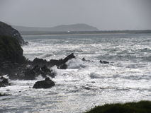 Waves crash on rocky shore line Stock Images