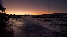 Waves crash on a walkway next to a lake royalty free stock images