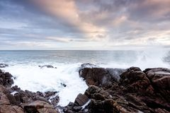 Waves crashes over rocks at the sunrises over the ocean in Northern Ireland stock photo