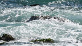 Waves crashing against boulders in sea