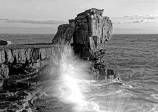 Waves crashing against cliff with landmark rocks in background Stock Photography