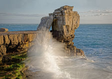 Waves crashing against cliff with landmark rocks in background Royalty Free Stock Images