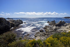 Waves are crashing against coastal rock formations. At California& x27;s pacific coast as the bright sun sparkles on the water royalty free stock photo