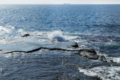 Rock in the Sea. Waves crashing against a large flat rock in the Mediterranean sea. A large freighter breaking the horizon Stock Photos