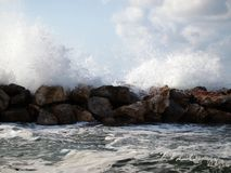Waves crashing against rocks and splashes fly around. Light storm on the sea. royalty free stock image
